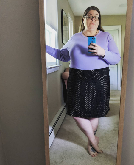 image of me in a full-length mirror in my guest room, with my hair down, wearing a black necklace, a lavender long-sleeved top, and a black skort with white polka dots