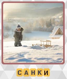 зимой в снегу мальчик везет свои санки