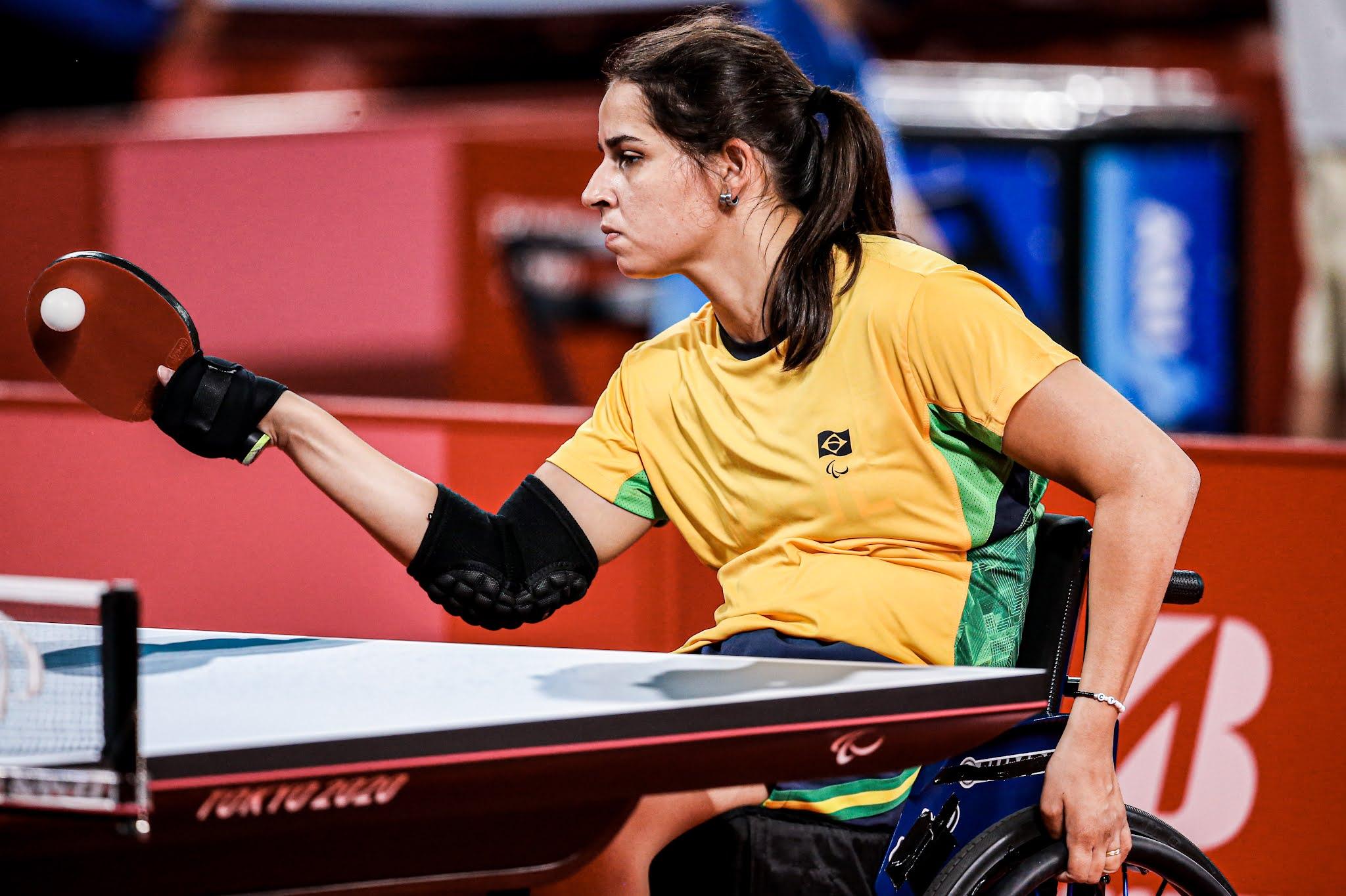 A mesa tenista Cátia Oliveira, de amarelo, rebate a bola branca com a raquete vermelha na mão direita, enquanto a outra mão está segurando a roda da cadeira de rodas, na qual a atleta está sentada