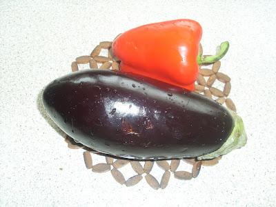 Μια μελιτζάνα και μια κόκκινη πιπεριά με σταγόνες δροσιάς πανω