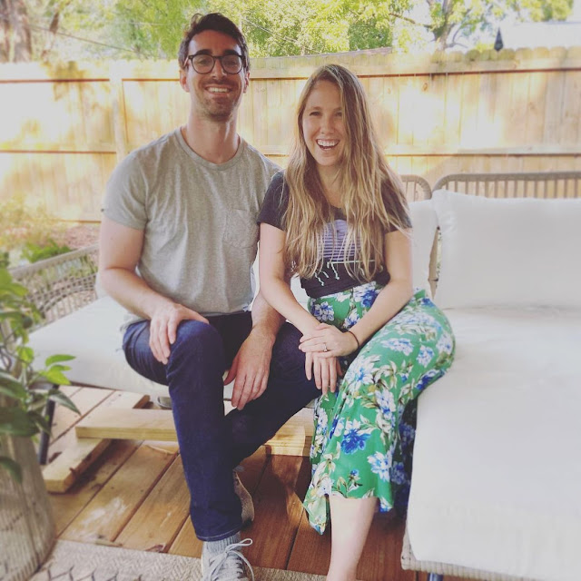 smiley man and woman sitting on a wooden bench in a sunny backyard with wooden fence and trees.