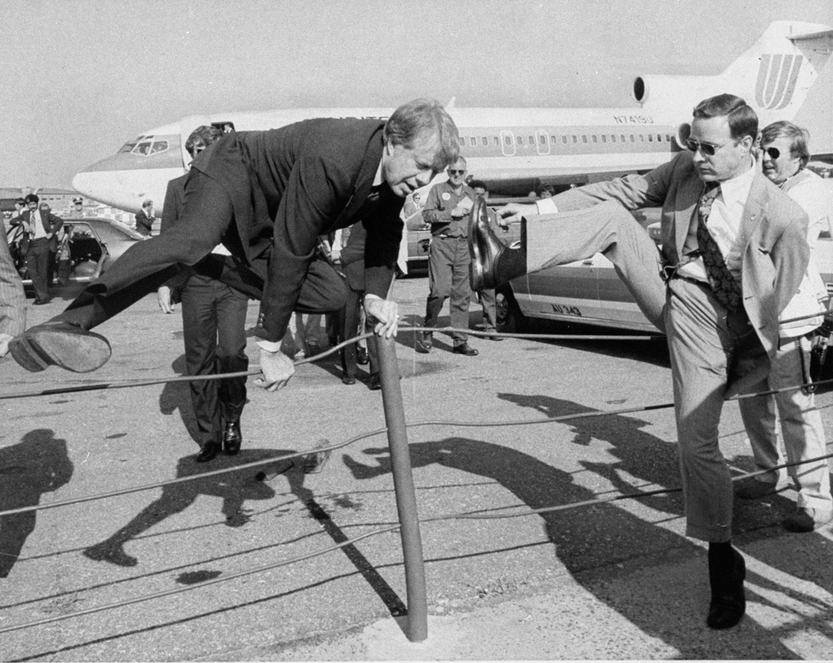 Jimmy Carter and an aide hop a fence at La Guardia to make a connection during the 1976 campaign