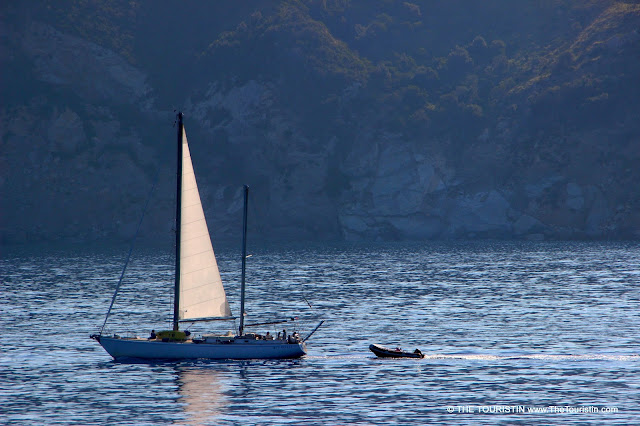 A small sailing boat towing a dinghy.