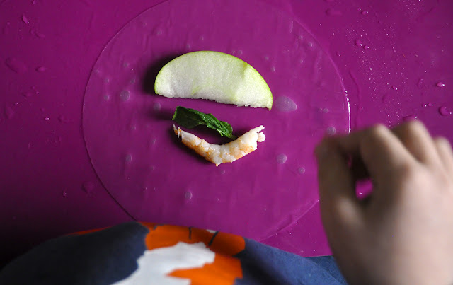 La oblea trasparente, con un trozo de manzana, una hoja de hierbabuena y una gamba