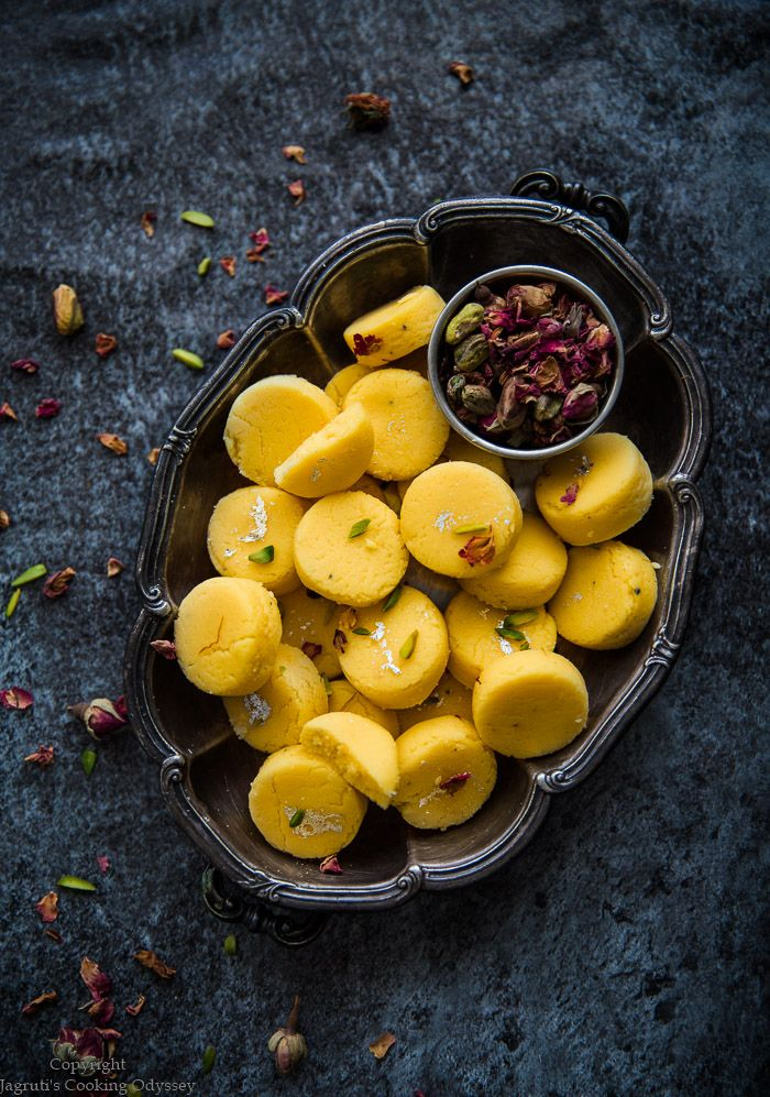 INSTANT KESAR PEDA IN A METAL TRAY NEXT TO BOWL OF ROSE PETALS AND PISTACHIO