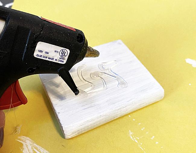 glue gun with glue on white wood scrap
