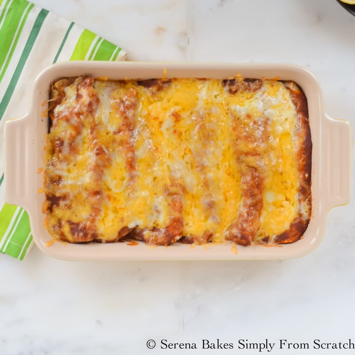 A pan of baked Chicken Enchiladas in Red Sauce.