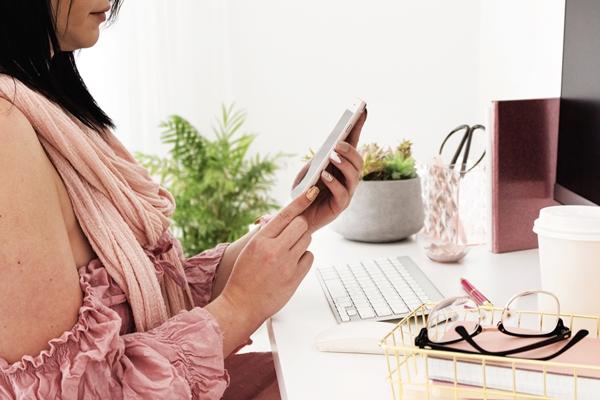 Mulher sentada em seu home office mexendo no celular