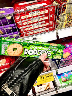 A picture of a white hand next to a black leather sleeve holding a rectangular box containing golden circular Jammie dodgers with a green filling with a light brown and green packaging with Jammie dodgers gooey apple in white font on a bright background