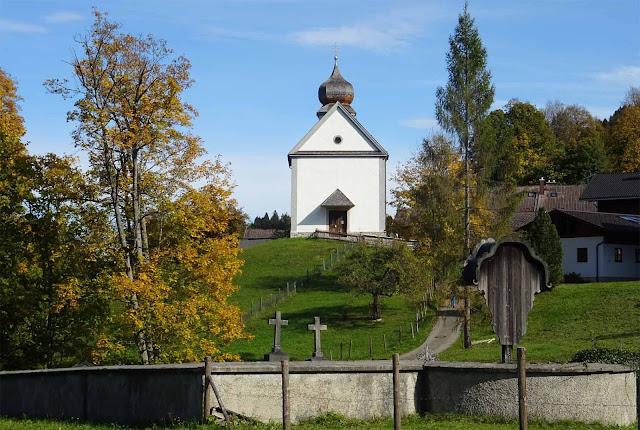 Friedhof und Kirchlein in Wamberg mit bunten Laubbäumen
