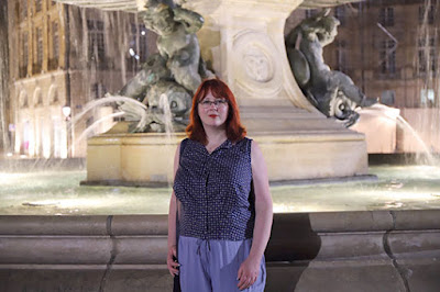 A redheaded woman standing in front of a fountain