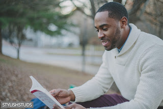 A guy is reading news paper, wearing a shawl collar sweater.
