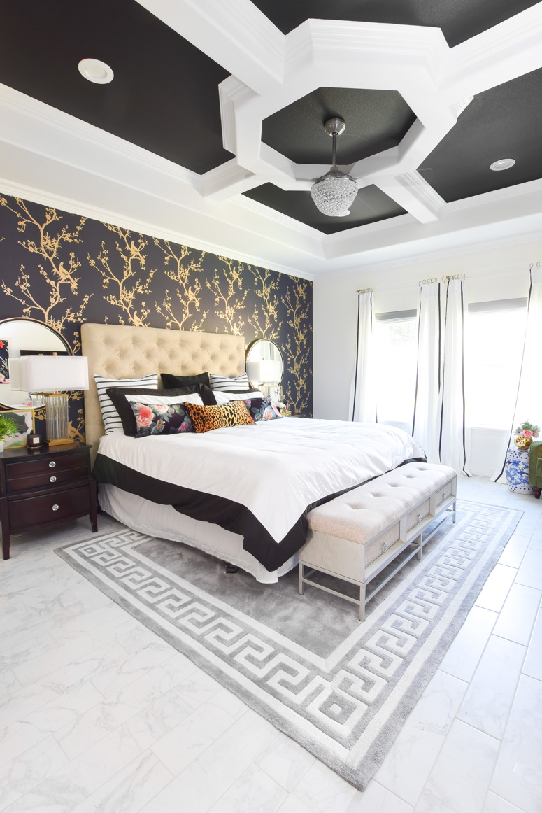 Tufted headboard in this black, white and gold master bedroom makeover paired with a grey Greek key rug and gorgeous tray ceiling.