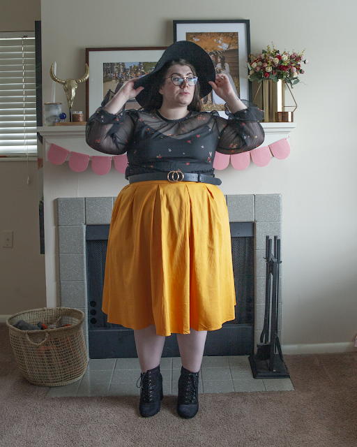 An outfit consisting of a black wide brim black hat, black sheer long sleeve microfloral dress as a top tucked into a yellow midi skirt and black lace up heeled boots.