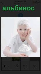 Мальчик альбинос сидя за столом ест мороженное и рукой подпирает свою щеку