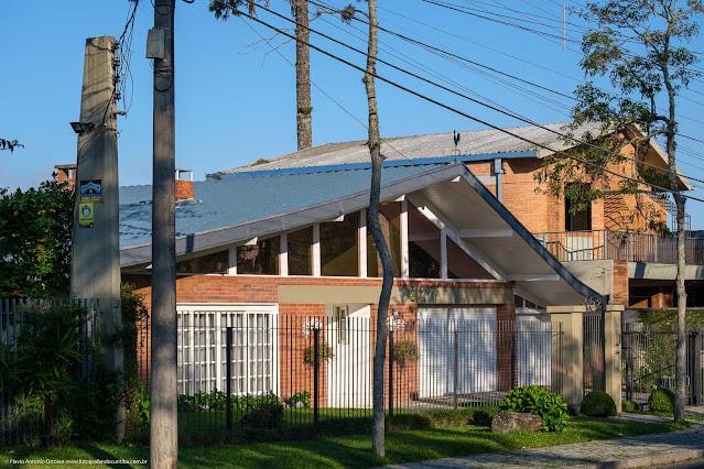 Fachada de casa modernista com galo dos ventos no telhado