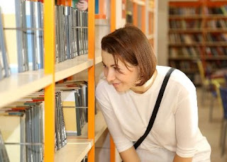 Smiling woman in front of bookshelves.