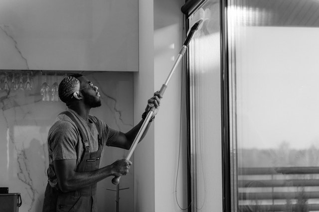 Man cleaning windows in a community apartment
