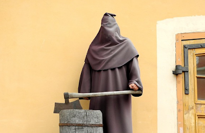 Hooded, axe-carrying executioner