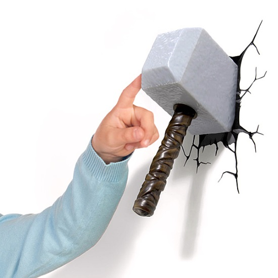 A lamp shaped like Thor's hammer protrudes from a white wall. Decals like black cracks surround it. A white hand attached to a pale blue sweater sleeve touches it for scale.