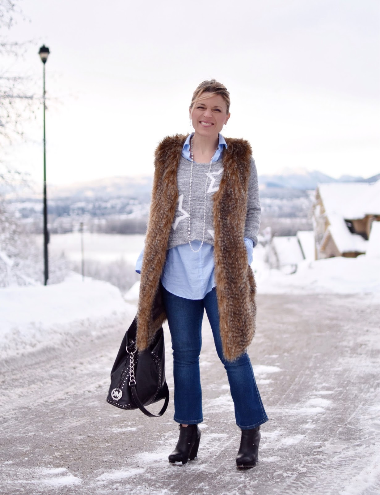 Monika Faulkner outfit inspiration - styling cropped jeans with an oversize-cuffed shirt, star-patterned sweater, and long faux-fur vest