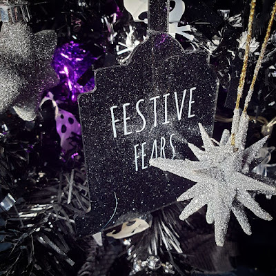 A black gilltery tombstone-shape cut from acrylic, with a transfer in white stylised spindly letters saying 'Festive Fears', suspended in a black Christmas tree, with a white star bauble in the foreground, and a grey six-pointed star bauble to the left. There is skull tinsel in the background