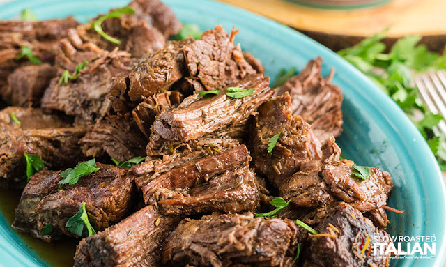 crockpot chuck roast on serving dish with fresh parsley