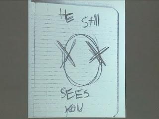 """スレンダーマンの顔と思しき落描き。""""HE Still SEES YOU""""とも書かれている。"""