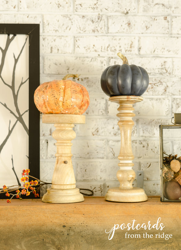 faux orange and blue pumpkins on top of tall wooden candle holders