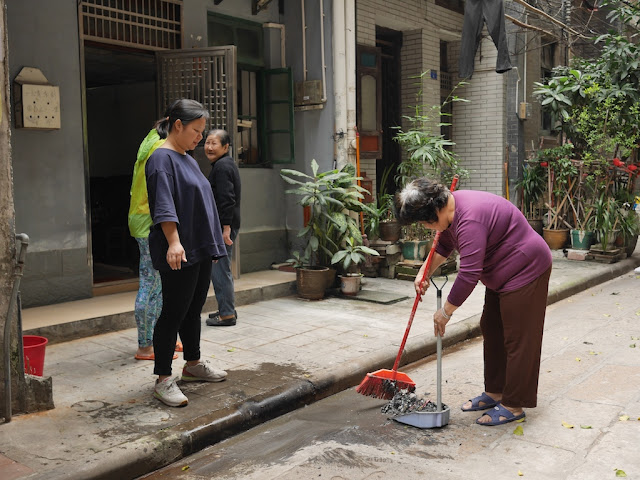 woman cleaning up ashes with broom and dustbin