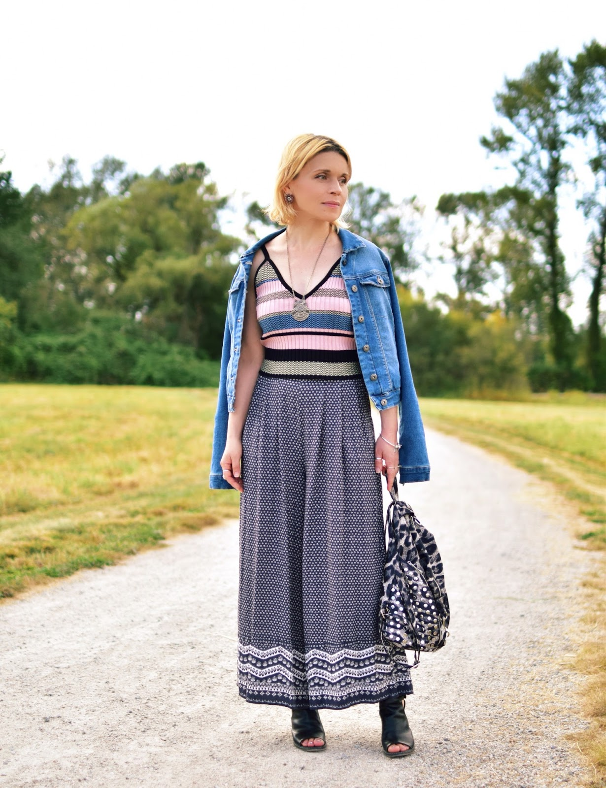 Monika Faulkner styles patterned palazzo pants with a striped tank top, denim jacket, and cut-out booties