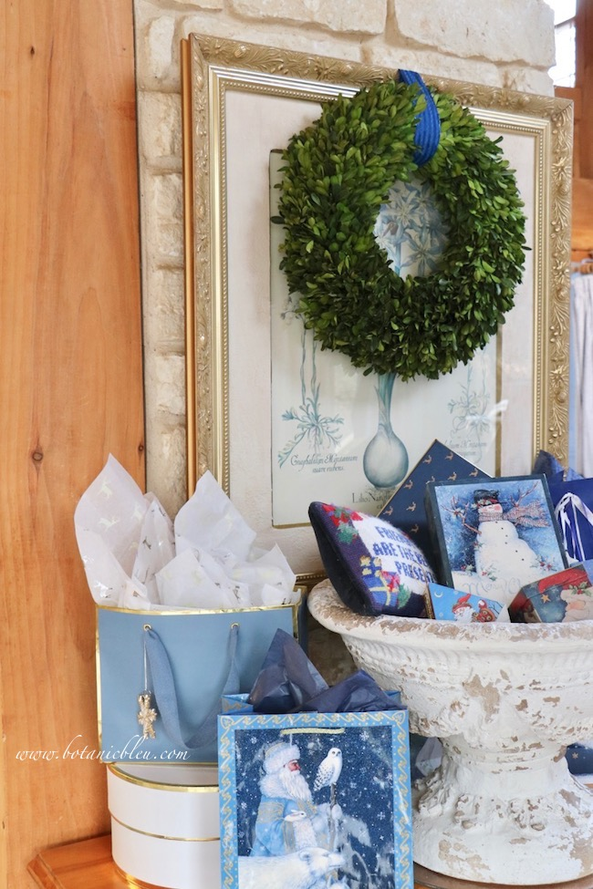 French country blue Christmas presents displayed in a white pedestal urn