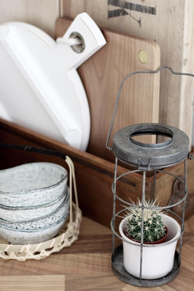 graue House Doctor Schälchen, daneben eine Kaktee und dahinter Küchenbrettchen von HK Living in weiß und Loods 5 in Holz