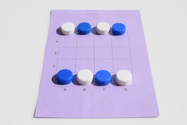 na zdjęciu widać planszę do gry Tac Tickle. Plansza jest w kolorze fioletowym i ma dwadzieścia pól oznaczonych w poziomie literami a w pionie cyframi. Na planszy leżą pionki, cztery w kolorze białym i cztery w kolorze niebieskim, naprzemiennie po obu stronach planszy. To ustawienie wyjściowe.