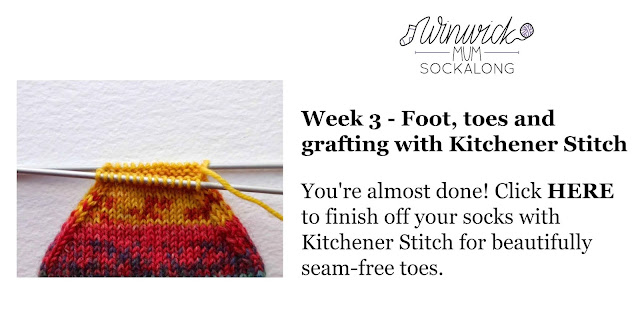 An orange and yellow striped sock on a pair of knitting needles.  The sock is almost finished!