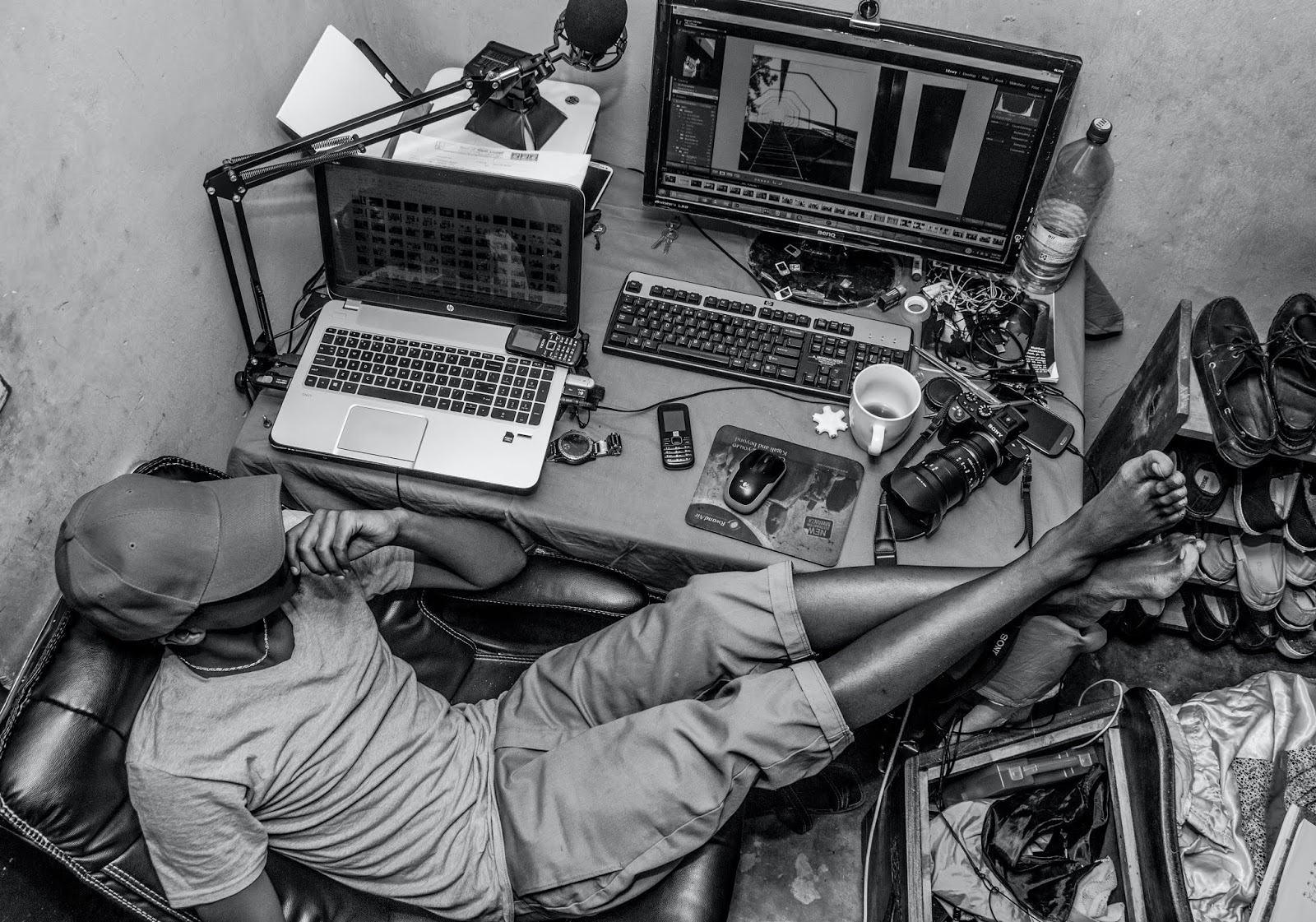 A photographer is editing his work in a small workspace