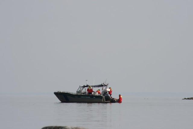 Pelastautumispukuisia henkilöitä veneen kyydissä