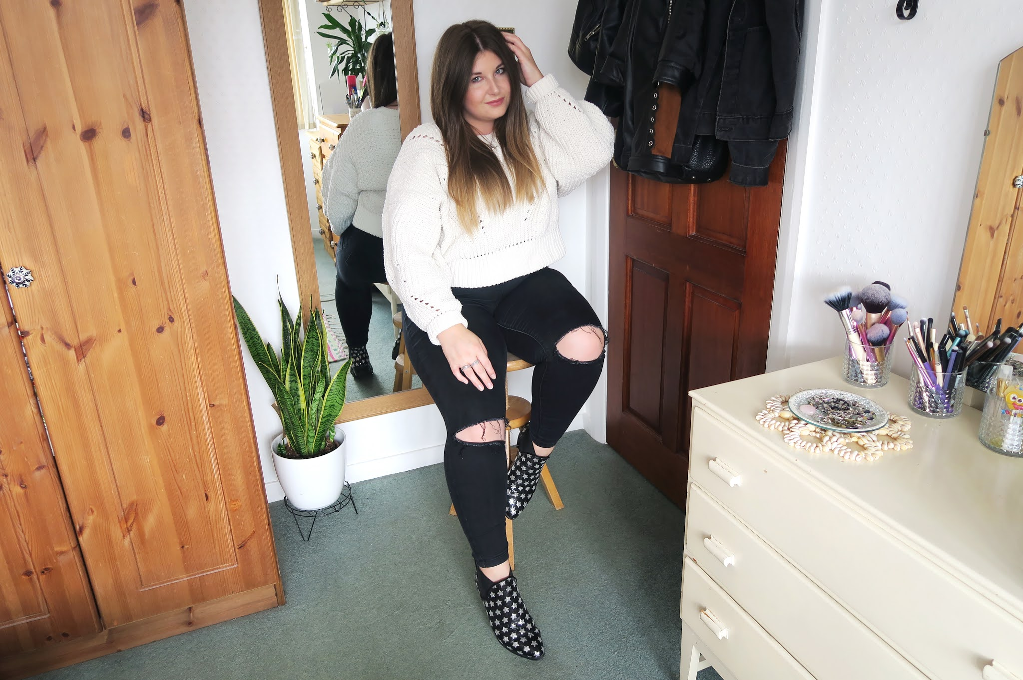 Grace is sitting on a wooden stool. She is wearing a pair of black ripped jeans and a white chunky jumper ready for the autumn weather
