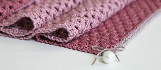 Close up of a lightly folded hand knit pink linen table runner with a pearl bead tied to the corner, on a white background.