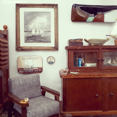 1/12 scale miniature living room with mid-century modern arm chair next to an early 20th century cabinet. Above the chair are three sailing-related pictures.