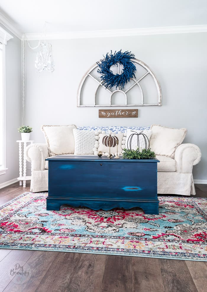 neutral sofa on multicolor rug, blue trunk and blue painted berry wreath on antique arch window