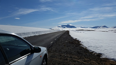 En vit bil står parkerad i vägrenen bredvid en framtinad asfalterad väg som kantas av snödrivor. I horisonten ser man snötäckta fjälltoppar.