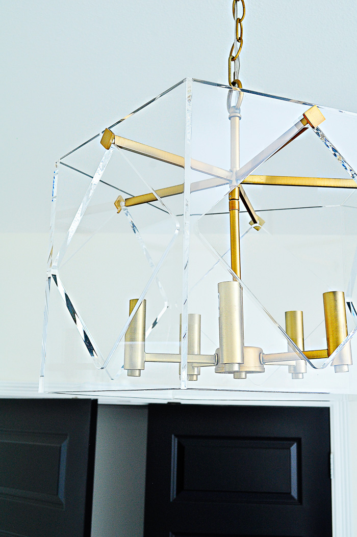 A lucite and brass chandelier in a white and black home office