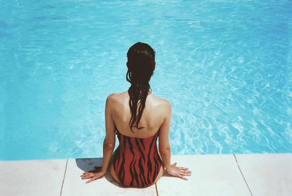 Mujer sentada en el borde de piscina