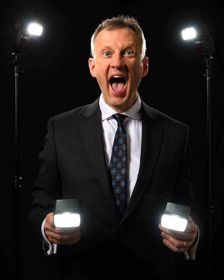 a photo of a man in a suit holding several camera flash units speed lights by daniel south