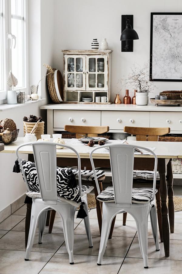 Kücheneinrichtung in Schwarz Weiß Holz mit leichten New Boho Elementen, weißer Küchentisch mit weißen Stühlen Voga