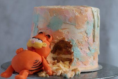 cake with watercolour smudge icing with a big chunk taken out of it and a fondant icing Garfield cat sitting next to it