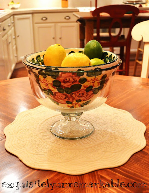 Lemons and limes in floral bowl on a table