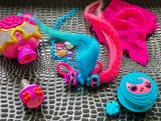 Showing the contents of the pop pop hair surprise including twin pets in purple with long blue hair and blue with long pink hair