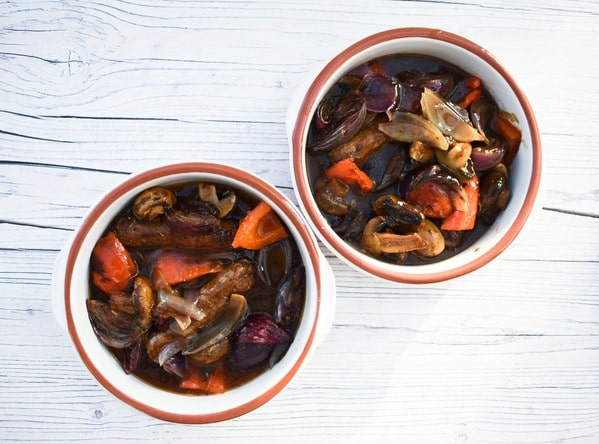The vegetables and sausage stew in two individual white ceramic dishes